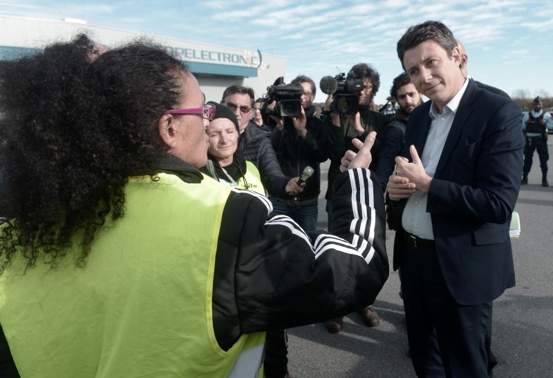 French Government's spokesperson Benjamin Griveaux (R) speaks with yellow vests protestors before an official visit, southwestern France, Nov. 29, 2018. (AFP Photo)