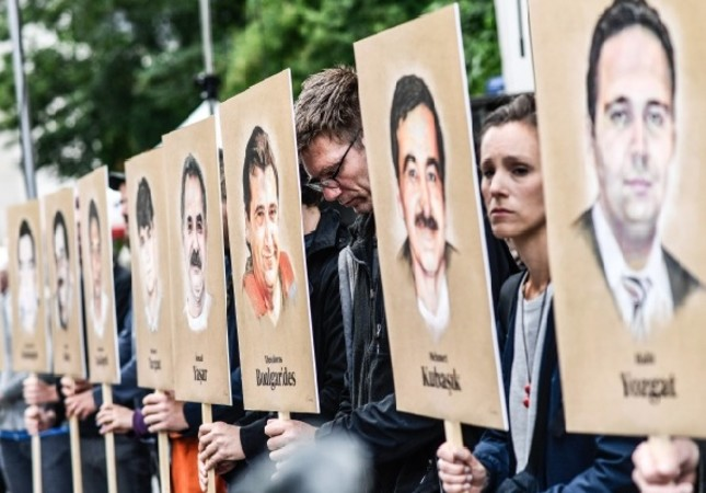 People hold banners with portraits  of migrants murdered by the racist NSU group, in front of the higher regional court in Munich, Germany, July 10.