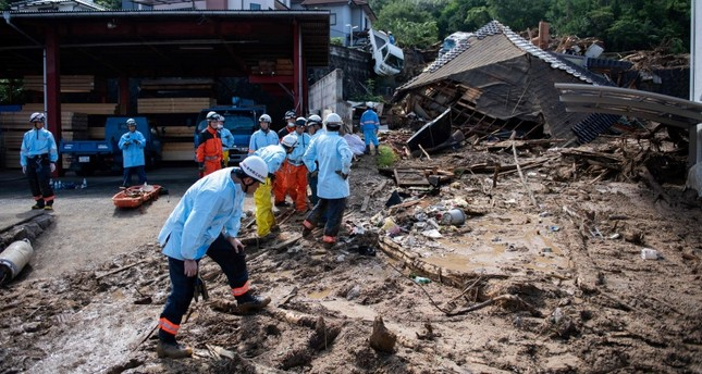 Rescuers clear debris scattered on a street in a flood hit area in Kumano, Hiroshima prefecture on July 9, 2018. (AFP Photo)