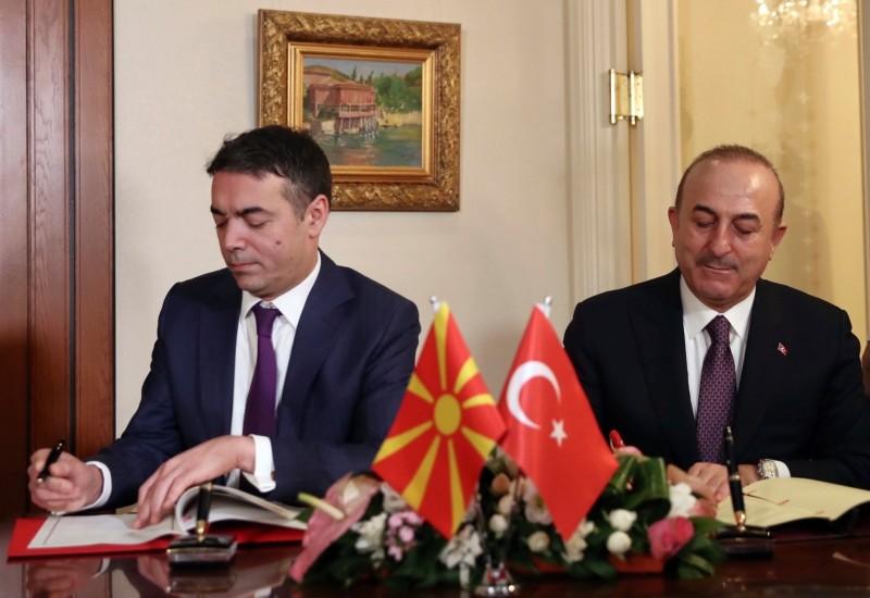 Turkey's Foreign Minister Mevlu00fct u00c7avuu015fou011flu, right, and Macedonia's Foreign Minister Nikola Dimitrov sign an agreement after their talks in Ankara, Turkey, Thursday, Jan. 17, 2019. (Turkish Foreign Ministry via AP, Pool)