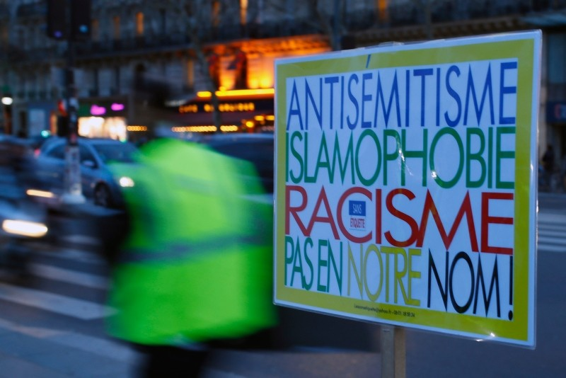 A poster reading ,Anti-Semitism, Islamophobia, Racism, Not in Our Name, during a gathering decrying anti-Semitism at Place de la Republique in Paris, Monday, Feb. 18, 2019, amid an upsurge in anti-Semitism in France. (AP Photo)