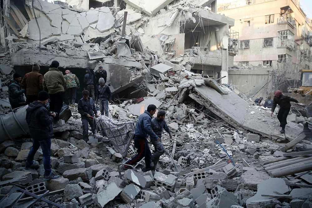 Civil defense workers evacuate victims from the rubble of a destroyed building following air strikes on the Eastern Ghouta town of Douma, on January 10, 2016. (AFP Photo)
