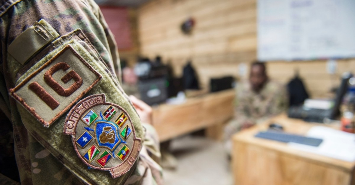 In this photo taken Feb. 24, 2018 and released by the U.S. Air Force, Tech. Sgt. Starr Day talks with service members during a battlefield circulation site visit at Camp Simba, Manda Bay, Kenya. (AP Photo)