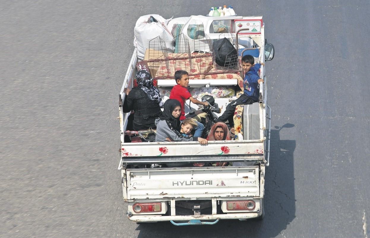 Residents of Idlib province flee toward the Syrian Turkish border, Sept. 10.