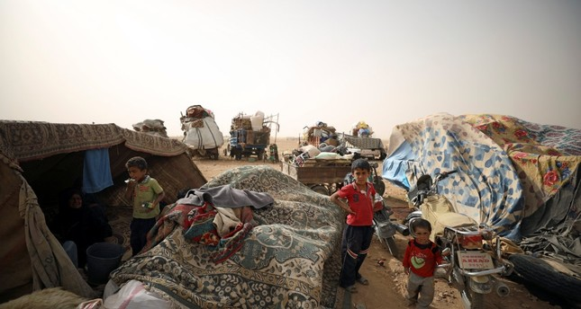 Internally displaced people who fled Raqqa, - the Syrian city devastated by the failed policies on the PYD and Daesh terrorists -, gather near vehicles carrying their belongings in a camp near Ain Issa, Syria, May 19.