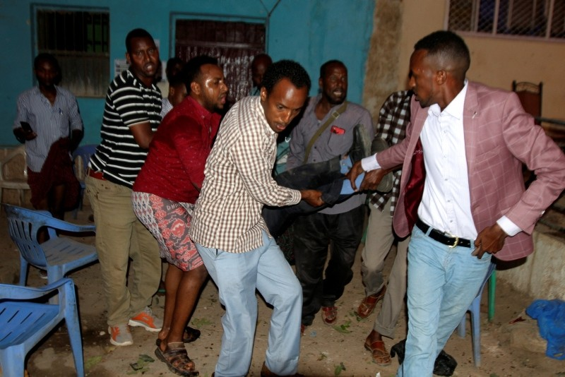 People carry a wounded man after a suspected suicide bombing in Baidoa, some 250km northwest of the capital Mogadishu, southern Somalia, 13 October 2018. (EPA Photo)