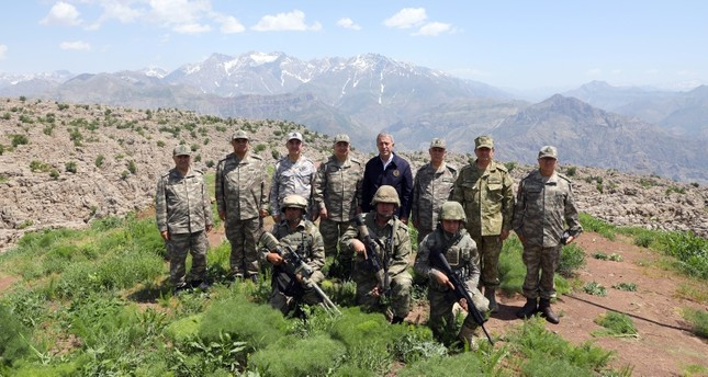 Defense Minister Hulusi Akar (4thR) and Turkish army, navy and air force commanders pose for a photo with soldiers serving at a military base in Derecik district of Hakkari, southeastern Turkey, June 5, 2019. (AA Photo)
