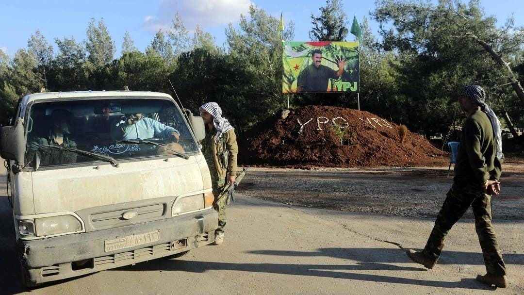 PYD terrorists stop a car, with PKK leader Abdullah u00d6calan's picture in the background (Reuters Photo)