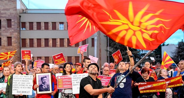 In this file photo taken on June 23, 2018 demonstrators wave flags in front of the parliament building in Skopje during a protest against the new name of the country, the Republic of North Macedonia. (AFP Photo)
