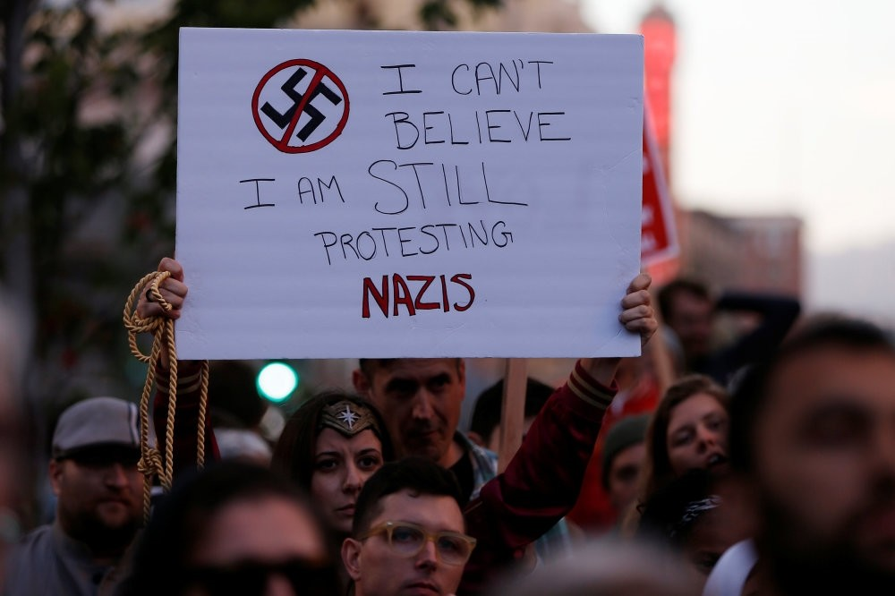 A demonstrator holds a sign during a protest in response to the Charlottesville car attack on counter-protesters after the ,Unite the Right, rally organized by white supremacists, Oakland, California, Aug. 12.