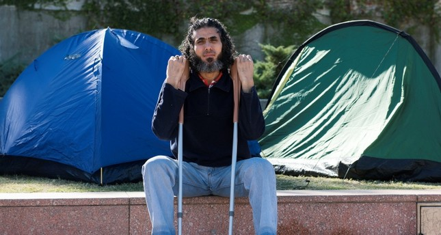 Former Guantanamo detainee Abu Wa'el Dhiab from Syria sits in front of the U.S. embassy while visiting former fellow detainees who were demanding financial assistance from the U.S., in Montevideo, Uruguay. AP Photo