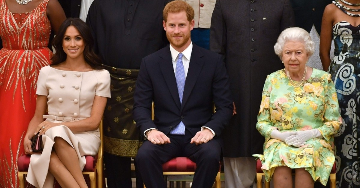Meghan Markle, Duchess of Sussex, Britain's Prince Harry, Duke of Sussex, and Britain's Queen Elizabeth II pose for a picture during the Queen's Young Leaders Awards Ceremony, June 26, 2018. (AFP Photo)