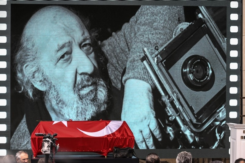 Slide shows and videos of Güler and his work are projected onto the screen at the memorial ceremony.