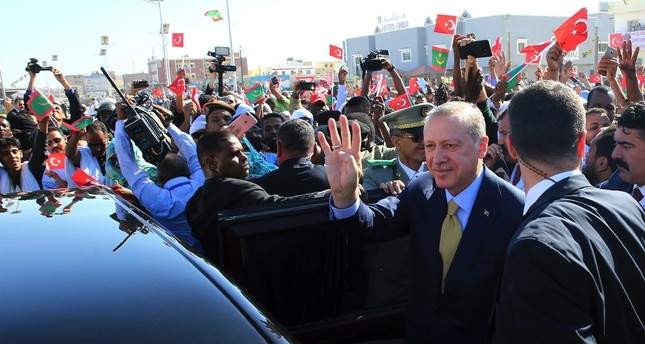 Turkish and Mauritanian security and people surround the car of President Erdoğan as he waves during a welcoming ceremony at the airport in Nouakchott, Mauritania, Feb. 28.