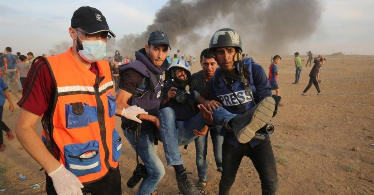 Palestinian paramedics and journalists carry a wounded fellow journalist, the Gaza Strip, Oct. 5, 2018. (AFP Photo)