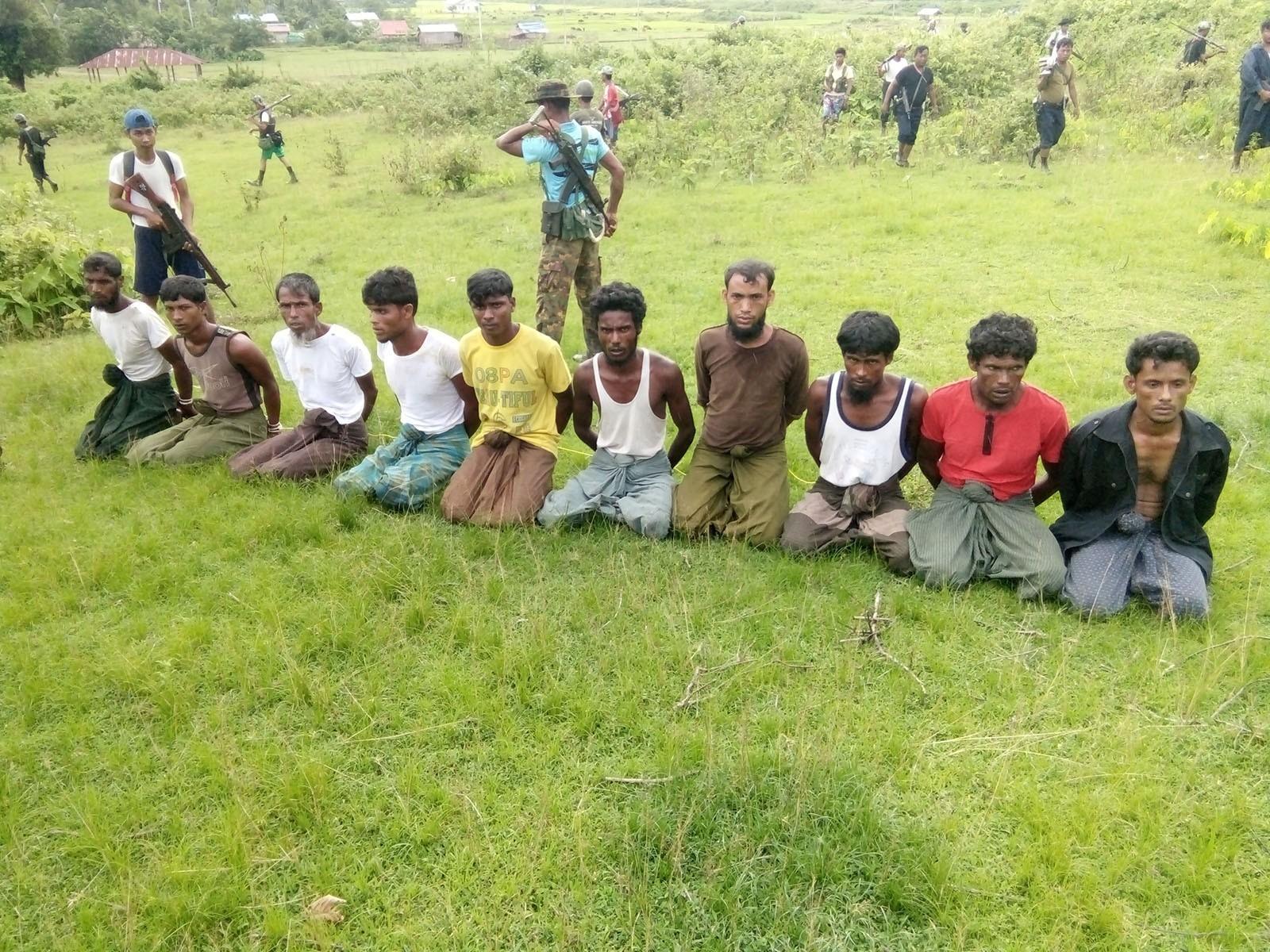 Ten Rohingya Muslim men with their hands bound kneel as members of the Myanmar security forces stand guard in Inn Din village September 2, 2017.