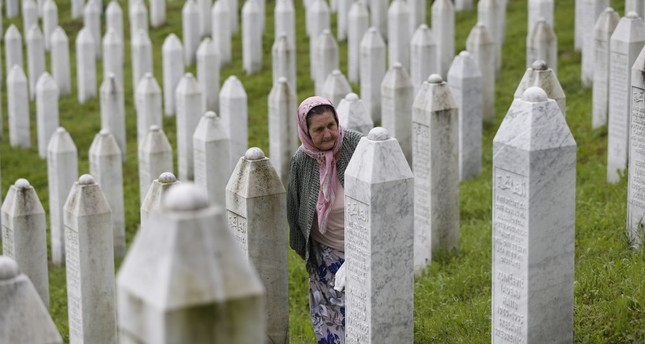 A Bosnian Muslim woman walks among gravestones at the memorial center of Potocari, Srebrenica, July 11, 2018.
