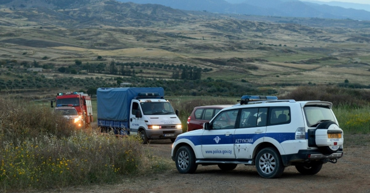 A police truck, rear left, carries a body found after Greek Cypriot investigators and police officers searched at a field outside of Orounta village, near Nicosia, Thursday, April 25, 2019