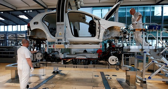 Workers assemble an e-Golf electric car at the new production line of the Transparent Factory of German carmaker Volkswagen in Dresden, Germany March 30, 2017. (Reuters Photo)