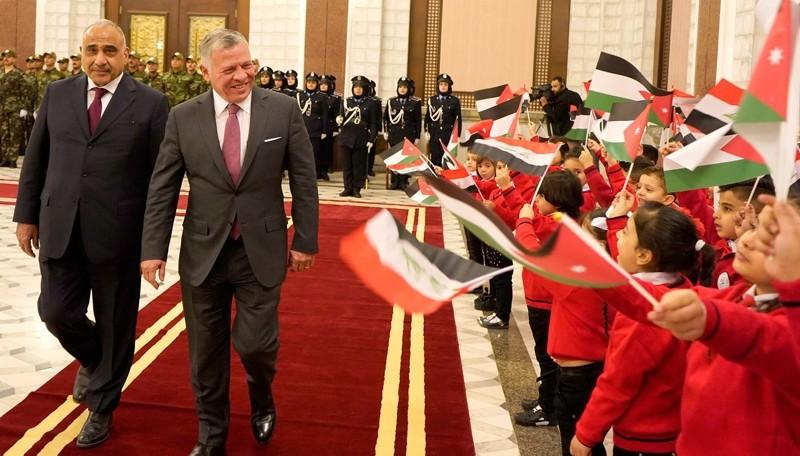 Children wave Iraqi and Jordanian national flags as Iraqi Prime Minister Adel Abdel Mahdi (L) welcomes Jordan's King Abdullah II in the Iraqi capital Baghdad on Jan. 14, 2019. (Jordanian Royal Palace / AFP)