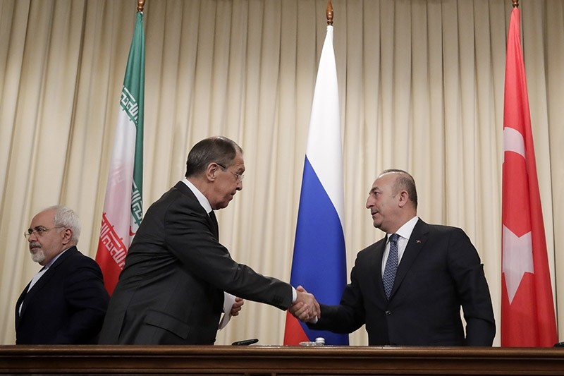 Russian FM Sergey Lavrov, (C), shakes hands with Turkey's FM Mevlu00fct u00c7avuu015fou011flu, as they and Iranian FM Mohammad Javad Zarif, (L), leave a joint news conference after their talks in Moscow, Russia, Tuesday, Dec. 20, 2016. (AP Photo)