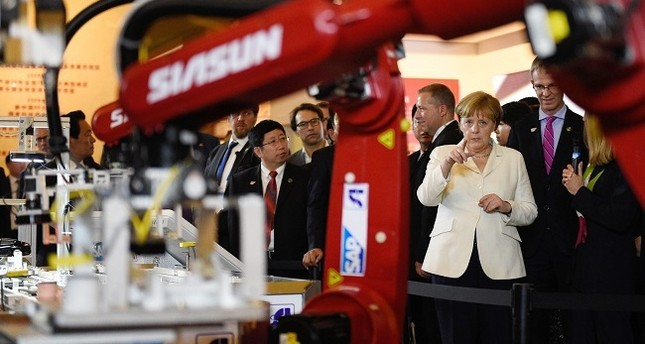 German Chancellor Angela Merkel (R) watches a presentation on industry 4.0 at the Industry Museum in Shenyang, China, 14 June 2016. (EPA Photo)