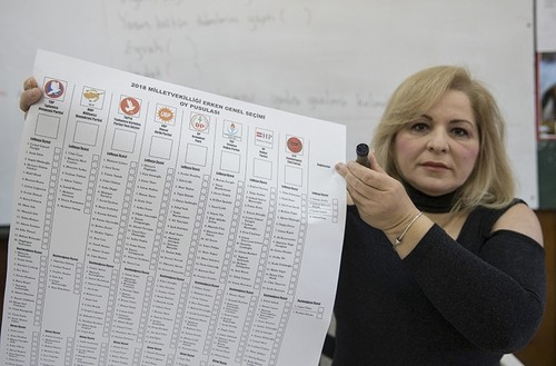 A woman holds a ballot showing political parties and candidates that Turkish Cypriots are voting for the snap polls (AA Photo)