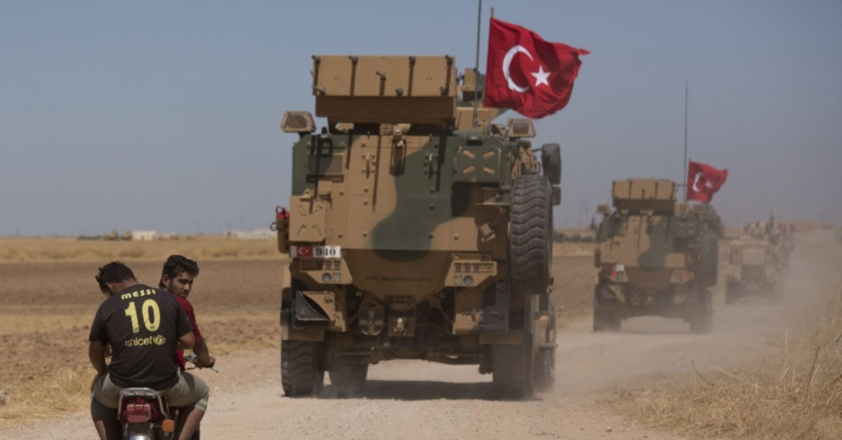 Two men on a motorbike follow Turkish and American forces as they conduct their first joint ground patrol in the so-called ,safe zone, on the Syrian side of the border with Turkey, , Sept. 8, 2019.