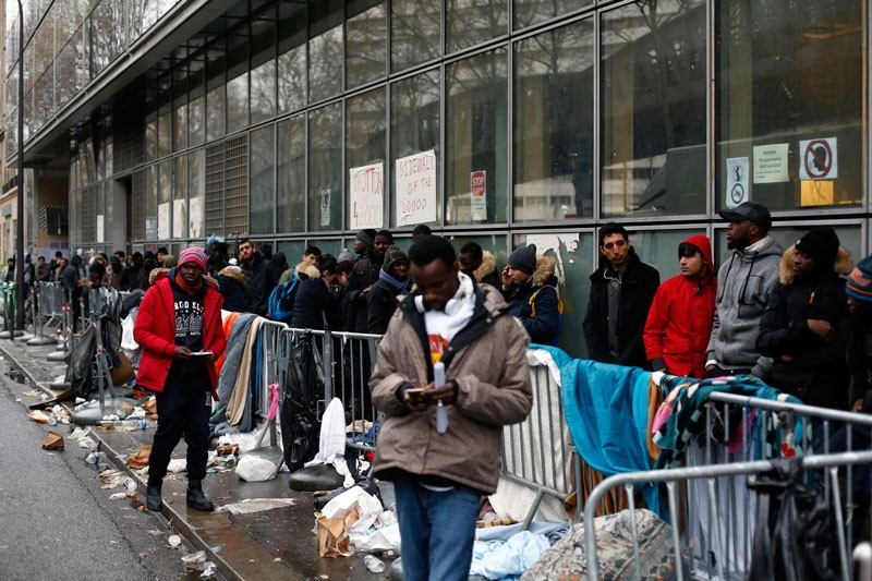 In this Dec.21, 2017 file photo, migrants queue outside a facility to apply for asylum, in Paris.  (AP File Photo)