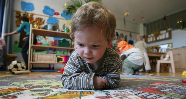 A German toddler of the Frogs group looks at a book at the Spreekita Kindergarten in Berlin 03 May 2007. AFP Photo