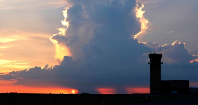 In this July 15, 2018 photo, the New Orleans Lakefront Airport air traffic control tower is seen in front of a sunset and a rain cloud over Lake Pontchartrain, in New Orleans (AP Photo)