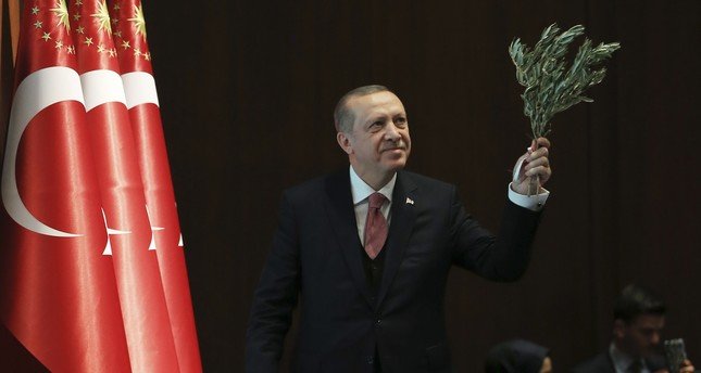 President Recep Tayyip Erdoğan holds an olive branch as he goes on stage to deliver a speech in Ankara.
