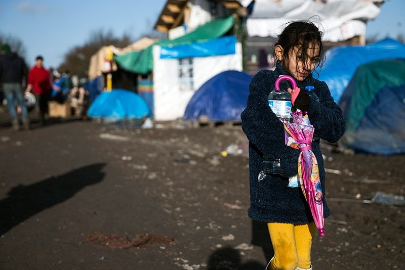 A young Kurdish girl walks along the muddy road framed with tents  and shacks in the makeshift migrant camp in grande-synthe near Dunkirk, France, Jan. 16, 2016 (EPA Photo)