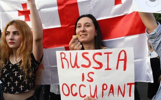 Protesters hold signs and wave Georgian national flags during a rally in front of the parliament building in Tbilisi, Georgia, June 21, 2019. (AFP Photo)