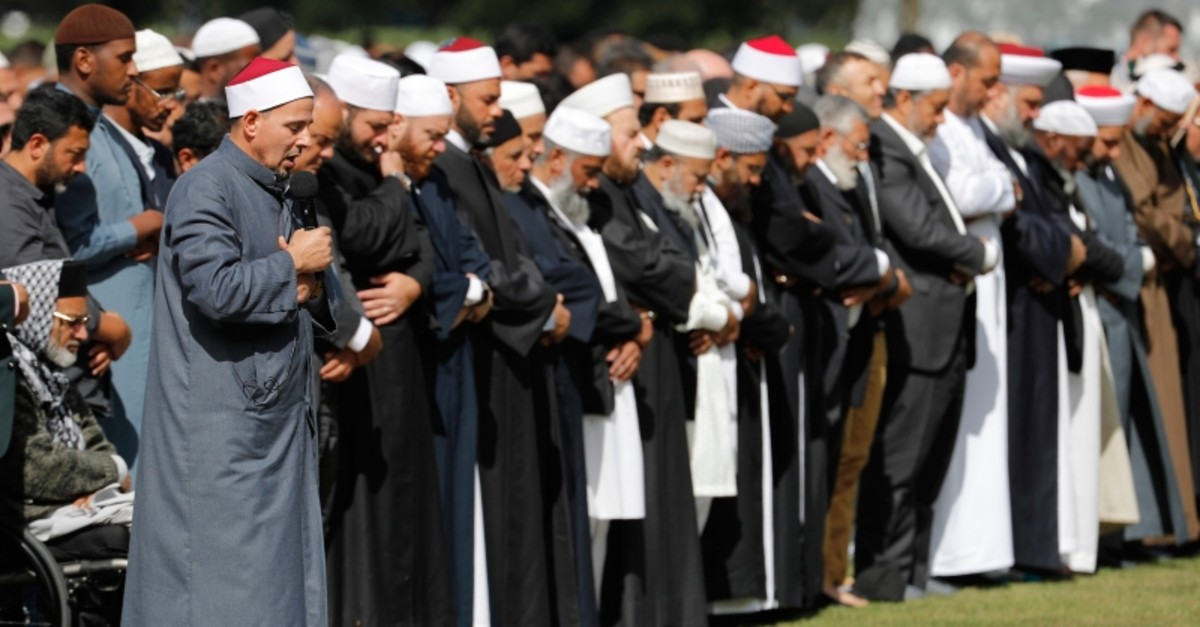 Imam Gamal Fouda, holding microphone, leads Friday prayers at Hagley Park in Christchurch, New Zealand, Friday, March 22, 2019. (AP Photo)