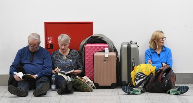 Passengers rest with their luggage at the Gatwick airport, after it reopens, in Sussex, December 21, 2018. (EPA Photo)