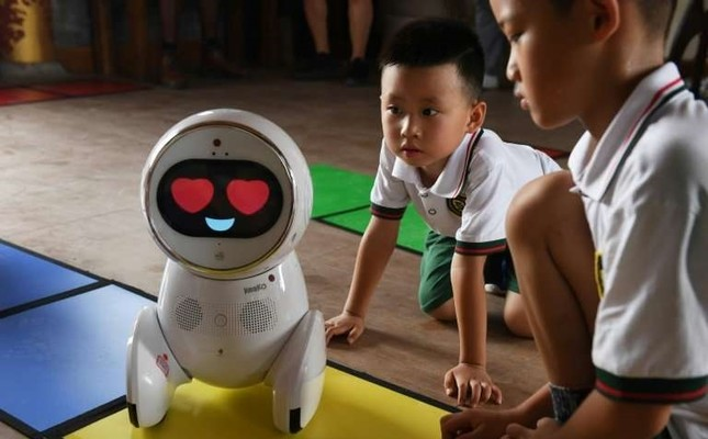 Children watch a Keeko robot make its way on a path they made from square mats at the Yiswind Institute of Multicultural Education in Beijing.