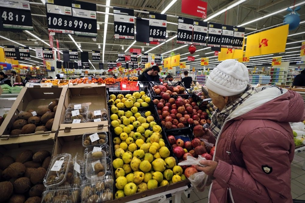 A Russian woman chooses Turkish fruits at a supermarket in St.Petersburg.Erdou011fan & Putin came up with solutions to bolster cooperation in energy and trade restrictions.Only item remaining open to negotiation,tomato still lingers over trade relations.