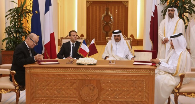 Macron (C-L), Qatari Emir Sheikh Tamim bin Hamad al-Thani (C-R) watch French Foreign Minister Jean-Yves Le Drian and his Qatari counterpart Mohammed bin Abdulrahman al-Thani (R) sign bilateral agreements in Doha on December 7, 2017. (AFP Photo)
