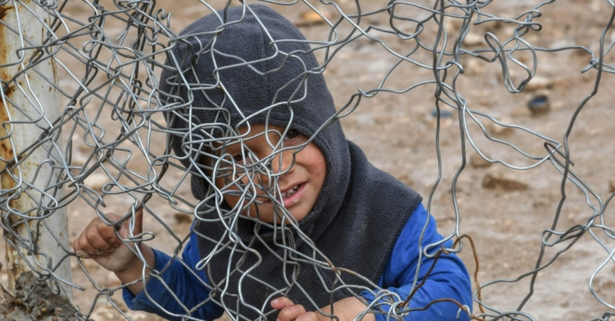 A child sits behind a wire fence in al-Hol camp, which houses relatives of Daesh terrorist group members, in al-Hasakeh governorate in northeastern Syria on March 28, 2019. (AFP Photo)
