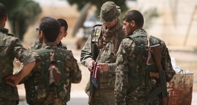 صورة ارشيفية لجندي أمريكي يحمل علم بلاده في يده، ويقف إلى جانب عناصر من قوات سوريا الديمقراطية