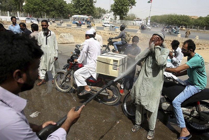 Pakistani volunteer spray water on people to keep them cool as temperatures reached 43 Celsius (109.4 Fahrenheit) in Karachi, Pakistan (AP Photo)