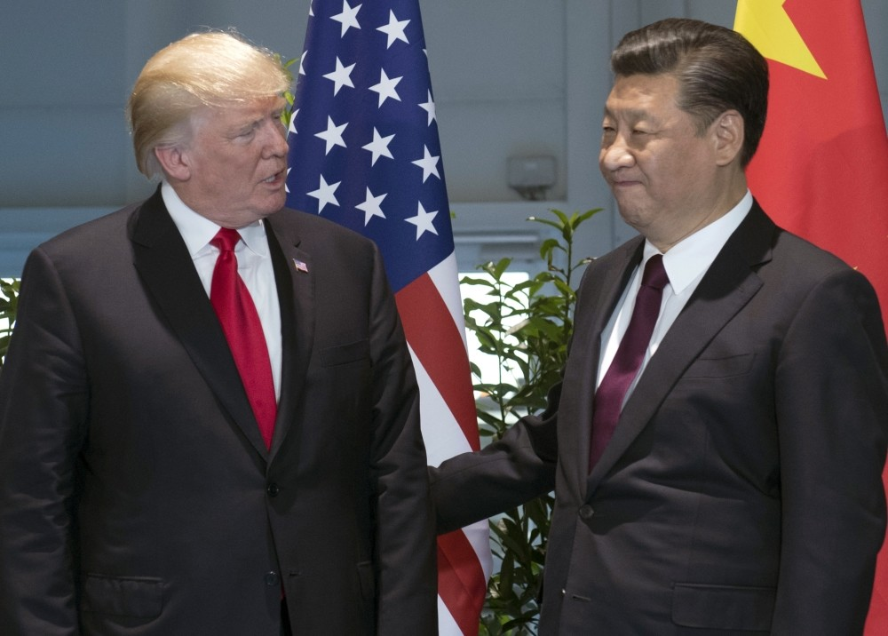 The President Trump (L) and Chinese President Xi arrive for a meeting on the sidelines of the G20 Summit in Hamburg, July 8.