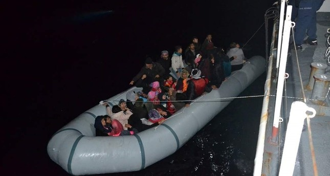 Afghan illegal migrants being pulled onto a Coast Guard boat, Ayvac?k, Nov. 2, 2019. (DHA Photo)