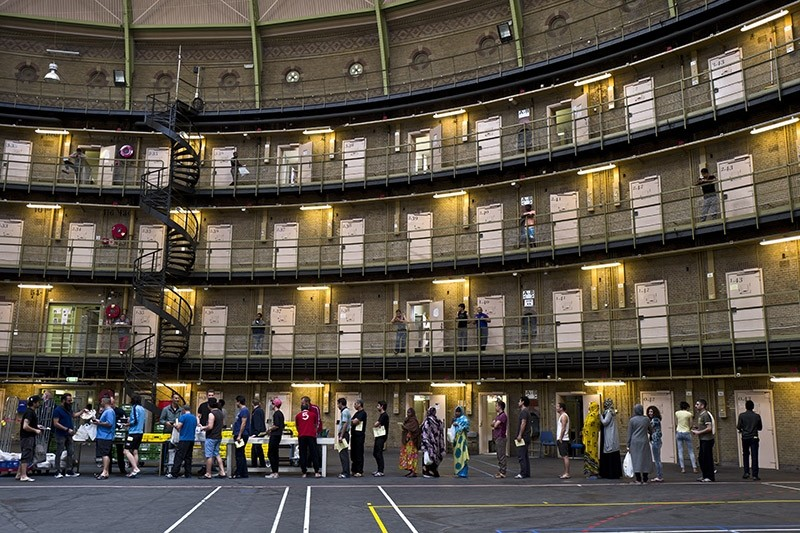 In this Wednesday, April 20, 2016 photo, refugees and migrants line up to receive their lunch at the former prison of De Koepel in Haarlem, Netherlands. (AP Photo)