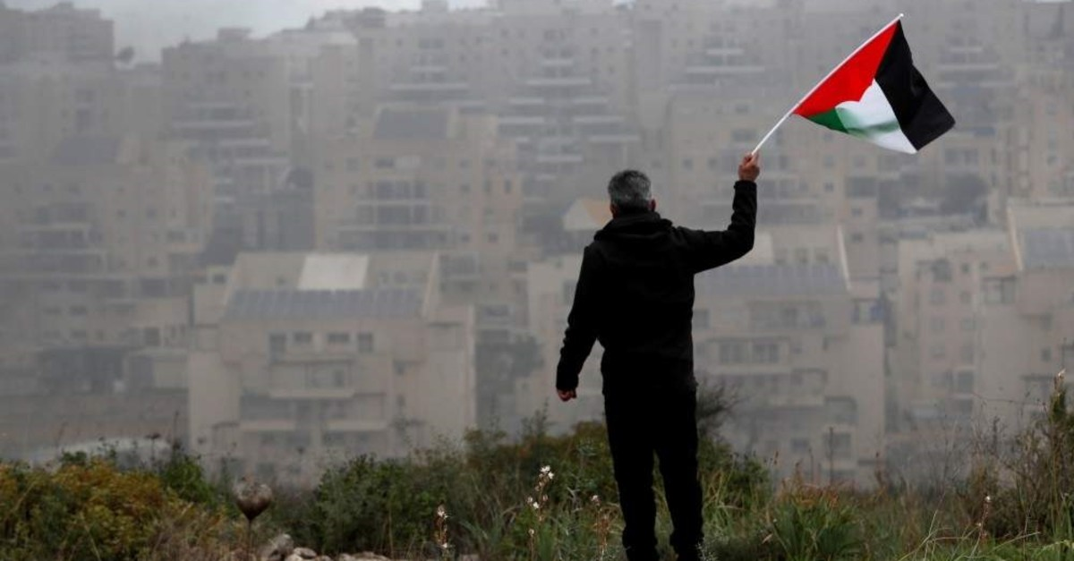 A demonstrator holds a Palestinian flag in the village of Bilin in the Israeli-occupied West Bank, Feb. 7, 2020. (REUTERS Photo)