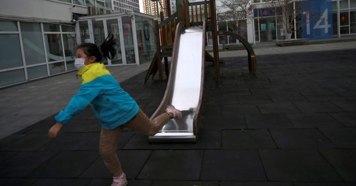 A child wearing a face mask plays near a slide at a commercial and residential complex, as China is hit by an outbreak of the novel coronavirus, in Beijing's central business district, China, Feb.18, 2020. (REUTERS)