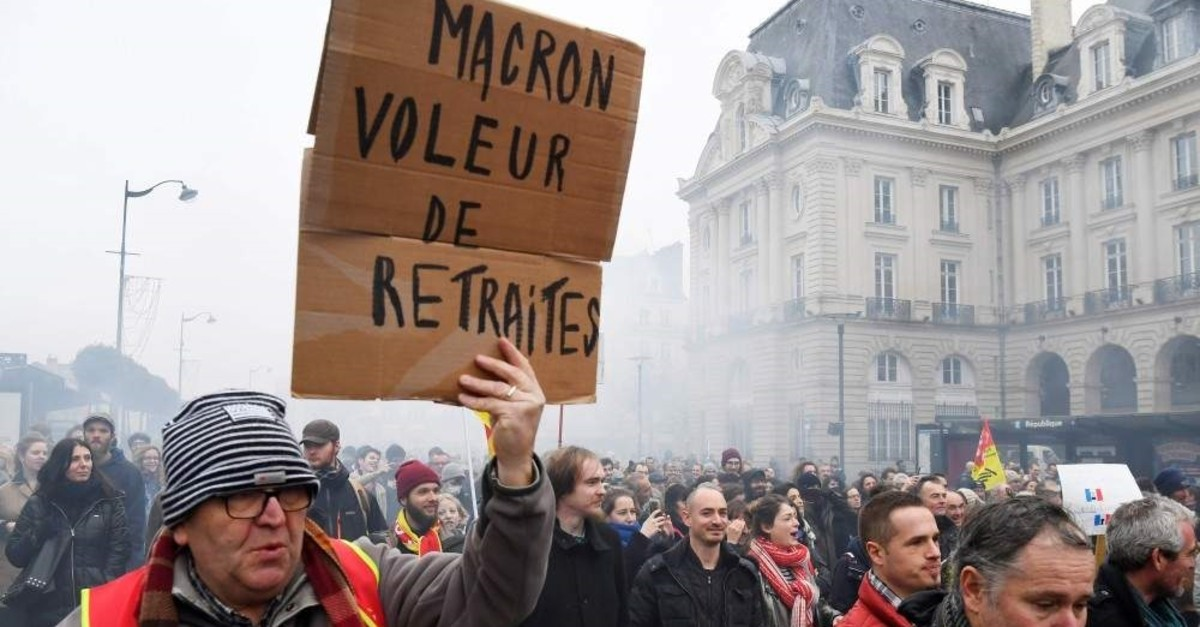 A protester holds a placard reading ,Macron = retirement thief, during a demonstration, Rennes, Dec. 17, 2019. (AFP Photo)