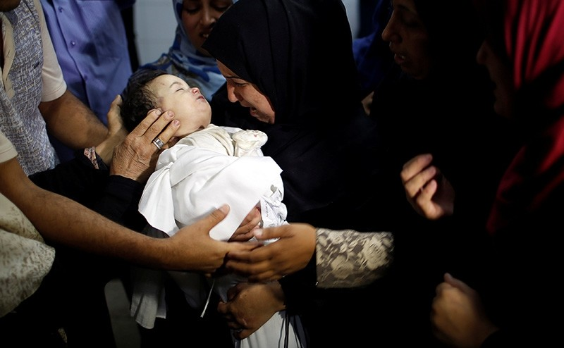 The mother of 8-month-old Palestinian infant Laila al-Ghandour, who died after inhaling tear gas during a protest at the Israel-Gaza border, mourns as she carries her body during her funeral in Gaza City May 15, 2018. (Reuters Photo)