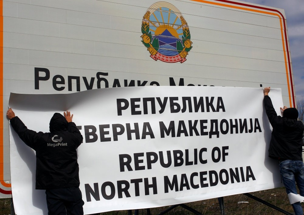 Workers put up a sign with Macedonia's new name, Gevgelija, Feb. 13, 2019.